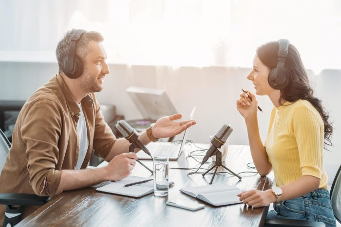 Two hosts in headphones talking while recording Airbnb podcasts