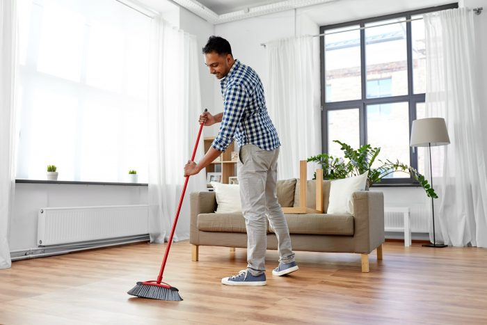 Man cleaning floor with Airbnb cleaning checklist