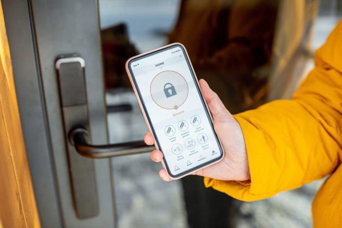 Person holding a phone with smart lock software for Airbnb key exchange